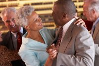 elderly African-American couple smiling and dancing