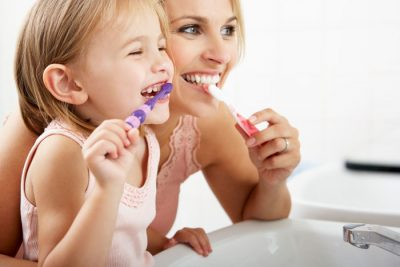 woman and child practicing good oral hygiene by smiling and brushing teeth
