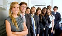 group photo of young professionals smiling in an office