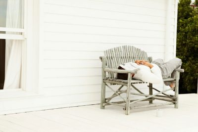businessman sick and sleeping on home wicker bench with newspaper over head