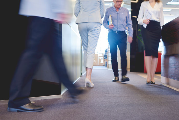 business people walking around crowded office space