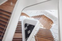 downward focused image of wooden stairs twisting at different levels with white walls and light