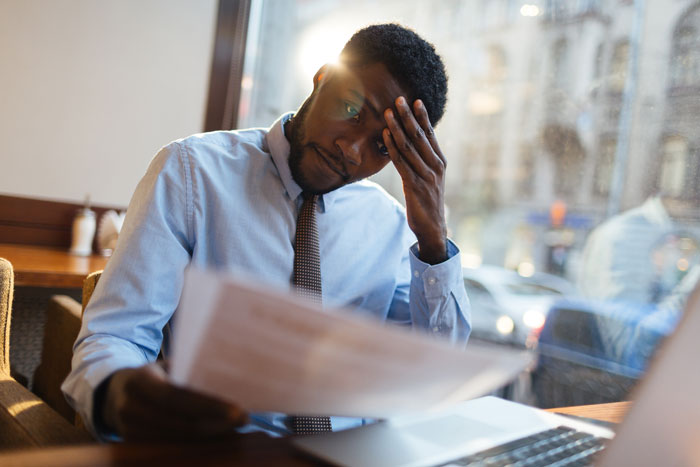 man sitting at desk stressed reading papers
